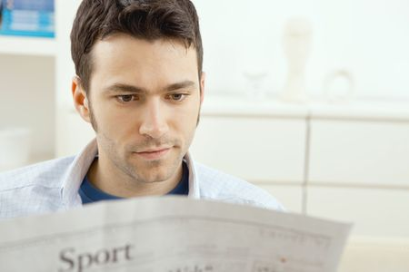Handsome young man sitting on couch at home reading sport news in newspaper. photo