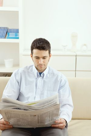 Handsome young man sitting on sofa reading newspaper at home. Stock Photo - 5982756