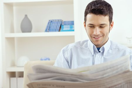 Happy young man sitting on couch reading newspaper at home, smiling. Stock Photo - 5982773