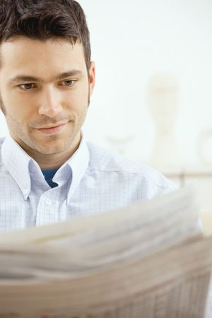 Handsome young man reading newspaper at home. Stock Photo - 5982772