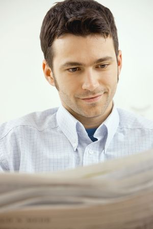 Handsome young man reading newspaper. Stock Photo - 5982779