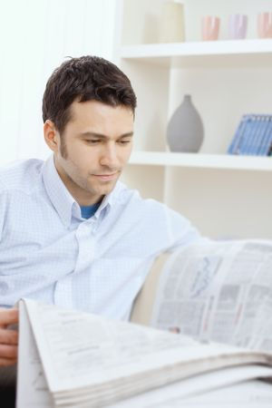 Handsome young man reading newspaper. Stock Photo - 5983005