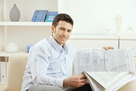 Casual young businessman reading business news, sitting on couch at home, looking at camera, smiling. photo