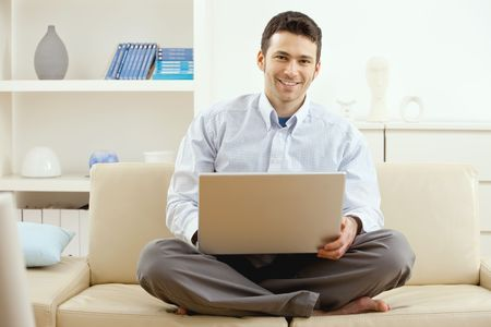 Happy young man sitting on couch and working on laptop computer at home, smiling. photo