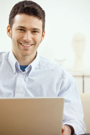 Happy young man working on laptop computer, smiling. Stock Photo - 5983049