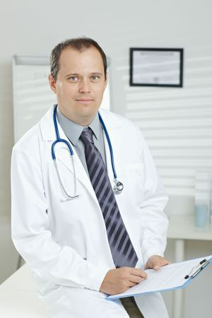fulfilled: Medical office -  middle-aged male doctor writing on clipboard, looking at camera, smiling.