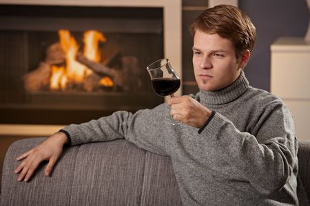 Young man sitting on sofa at home on a cold winter day in front of fireplace, drinking red wine. photo