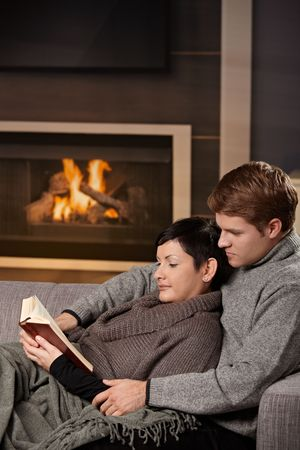 tea cosy: Young couple hugging on sofa in front of fireplace at home, reading book. Stock Photo