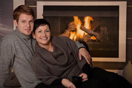 Young couple hugging in front of fireplace at home, looking at camera, smiling. photo