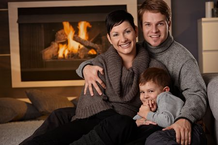 Happy family sitting on couch at home in a cold winter day, looking at camera, smiling. photo