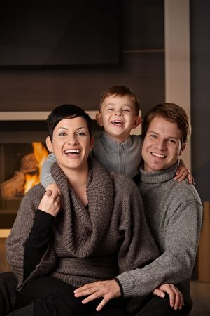 warm cloth: Happy family sitting on couch at home in a cold winter day, looking at camera, laughing.
