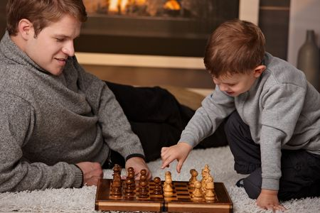 Father and 4 years old son playing chess at home in a cold winter day. photo