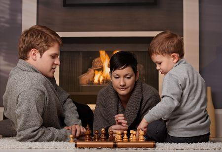jugando ajedrez: Joven de la familia con un ni�o de 4 a�os de edad, jugar al ajedrez en casa en un d�a de invierno.