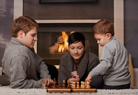 Young family with 4 years old kid playing chess at home in a cold winter day. Stock Photo - 5983208