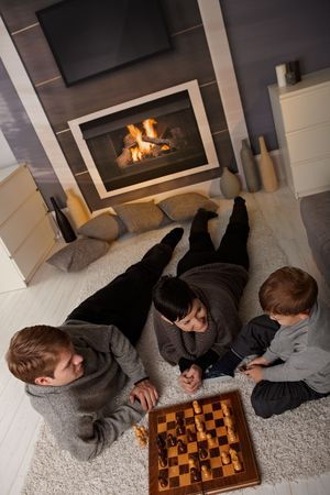 Young family with 4 years old kid playing chess at home in a cold winter day. Stock Photo - 5983197