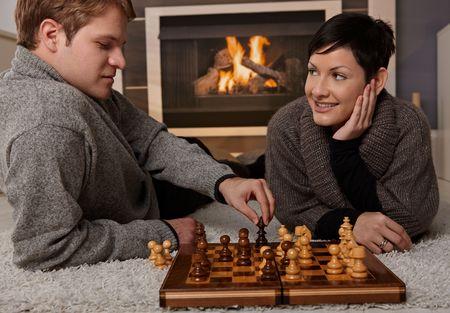 colores calidos: Joven pareja de jugar al ajedrez en casa en un d�a de invierno. Foto de archivo