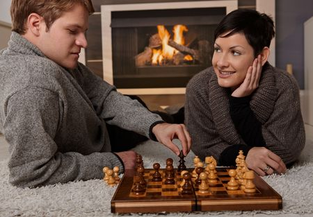 warm cloth: Young couple playing chess at home on a cold winter day. Stock Photo
