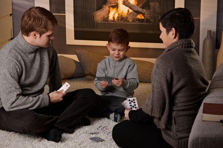 colores calidos: Joven de la familia con un ni�o de 4 a�os de edad, jugando el juego de cartas en casa en un d�a de invierno. Foto de archivo