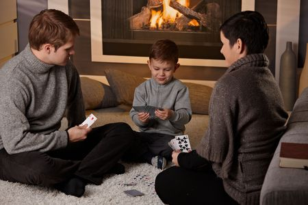 warm cloth: Young family with 4 years old kid playing card game at home in a cold winter day.