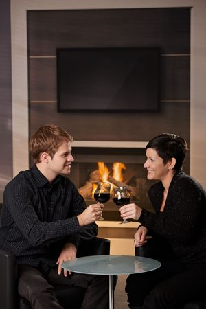 Young romantic couple dating, sitting in front of fireplace at home, drinking red wine. Stock Photo - 5983169