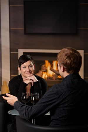 Young romantic couple dating, sitting in front of fireplace at home, drinking red wine. Stock Photo - 5983173