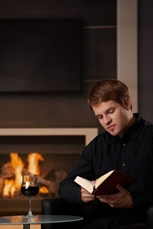 Young man sitting in front of fireplace at home on a cold winter day, reading book. Stock Photo - 5983170