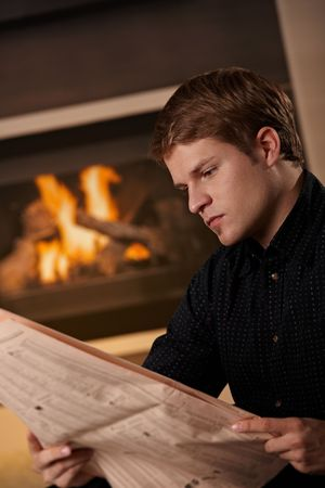 Young man sitting in front of fireplace at home on a cold winter day, reading newspaper. photo