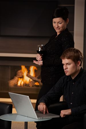 Young man sitting in front of fireplace at home working on laptop computer, woman standing behind. photo