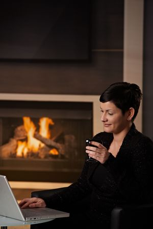 telework: Young woman sitting in front of fireplace at home on a cold winter day, working on laptop computer.
