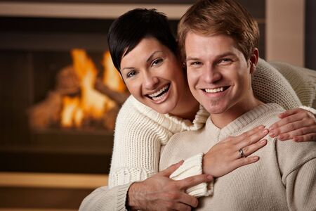 warm cloth: Happy young couple hugging in front of fireplace at home, looking at camera, smiling. Stock Photo
