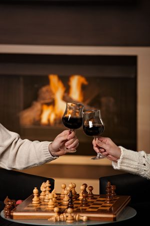 Hands holding glass of red wine, clinking in front of fireplace. photo