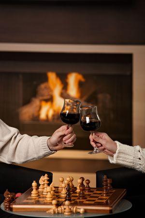 clinking: Manos sosteniendo el vaso de vino tinto, chocan en frente de la chimenea.