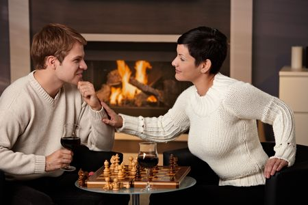Young couple playing chess at home on a cold winter day. Stock Photo - 5983196
