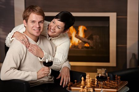 Happy young couple hugging in front of fireplace at home, looking at camera, smiling. Stock Photo - 5983202