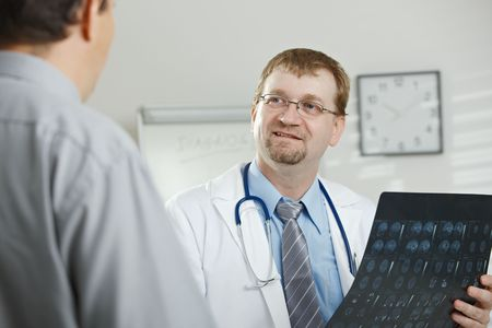 Medical office - middle-aged male doctor explaining computer tomograph scan to patient. photo