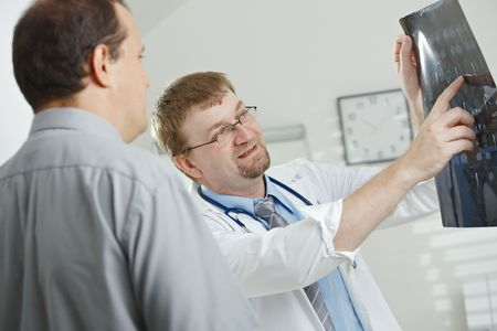 Medical office - middle-aged male doctor explaining computer tomograph scan to patient. Stock Photo - 5983130