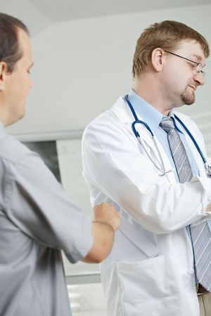 Medical office - patient bribing doctor, putting money in envelope to pocket. photo