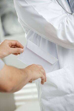 Medical office - patient bribing doctor, putting money in envelope to pocket. Stock Photo - 5988146