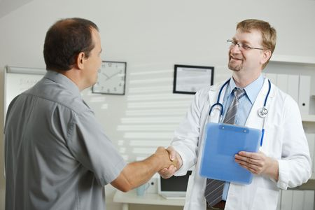 doctor and patient: Medical office - middle-aged male doctor greeting patient, shaking hands.