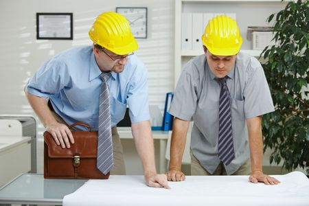 Architects working at office - planning and looking at blueprint on desk. Stock Photo - 5983164