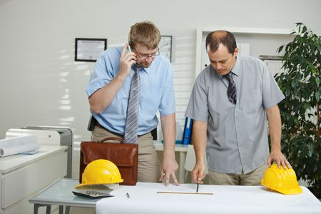 Architects working at office - planning and looking at blueprint on desk. Stock Photo - 5983165