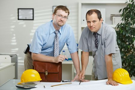 Architects working at office - planning at desk, looking up. Stock Photo - 5983166
