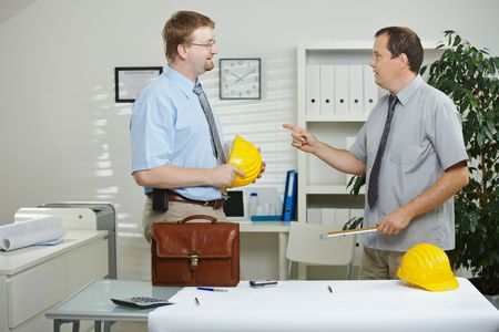 Engineers working at office - planning and talking over blueprint on desk. Stock Photo - 5983156