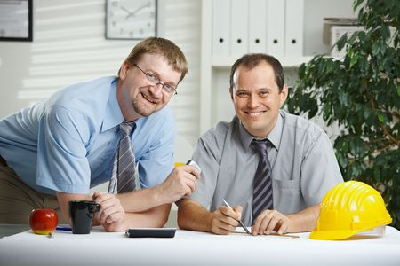Architects working at office - planning on desk, looking at camera, smiling.  photo