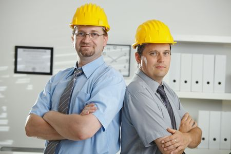 undoubting: Engineers in hardhats posing for teamphoto at office.  Stock Photo