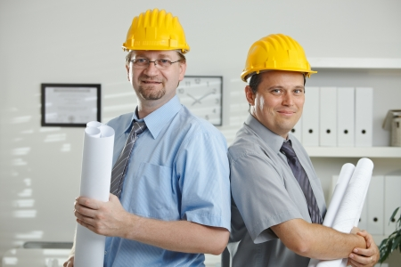 gratified: Architects in hardhats posing for teamphoto at office.