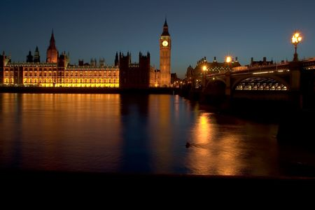The famous landmarks of London: The Parliament, the Big Ben and the Thames by night. photo