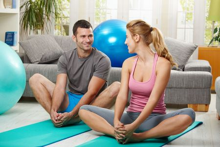 warm up exercise: Young couple warming up before training, sitting on fitness mat, looking at each other smiling.