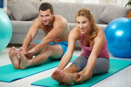 Young couple sitting on fitness mattress and streching legs before treining photo