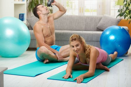 Young women doing streching exercise on fitness mat, muscular man drining water in the background. Selective focus on woman. photo